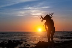 Silhouette of flexible girl with dreadlocks on ocean coast. During amazing sunset Royalty Free Stock Image