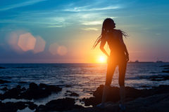 Silhouette of flexible girl on the sea coast. During a amazing sunset Stock Images