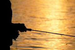 Silhouette of fly fisherman at sunset. Silhouette of fly fisherman casting for rainbow trout during a beautiful summer evening Royalty Free Stock Photo