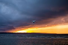 Flying drone over sea and cloud sky. Silhouette of a flying drone in clouds sky on a background of sea sunset royalty free stock photography
