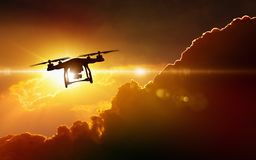 Silhouette of flying drone in glowing red sunset sky. Modern technological background - silhouette of flying drone in glowing red sunset sky stock photography