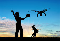 Silhouette of a flying drone, and a man with a remote control and dog at sunset. royalty free stock photo