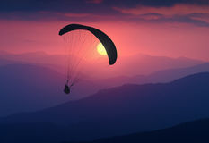 Silhouette of flying paraglide in a light of sunrise. Above the misty mountain valley Stock Photos