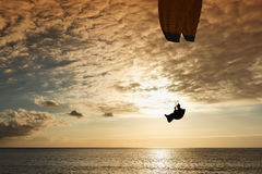 Silhouette of flying paraglider Stock Image