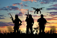 Silhouette flying reconnaissance drone over city in a smoke and a terrorists Stock Image