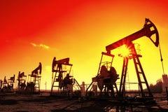 Silhouette fonctionnante de pompes de pétrole dans la ligne Photographie stock