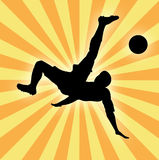 Silhouette of football player man kicking ball. Against yellow stardust background Stock Images