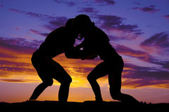 Silhouette of football players hitting. A silhouette of football players hitting one another Royalty Free Stock Image