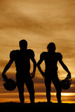 Silhouette of football players holding helmets in the sunset Royalty Free Stock Photography