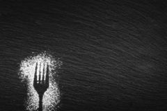 Silhouette of a fork and a spoon drawn with white flour stock images