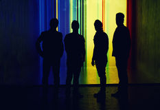Silhouette of four people standing on highlighted wall background Royalty Free Stock Photography