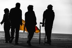 Silhouette of four people near the coast. Silhouette of four people standing near the beach with a color flag bewteen them stock photo
