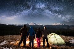 Silhouette of four people standing together beside camp and tent under beautiful night sky full of stars and milky way Stock Photography
