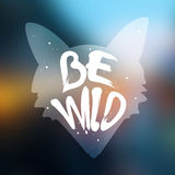 Silhouette of fox with lettering text Be Wild on blur background. Vector label Royalty Free Stock Photos