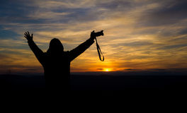Silhouette of free and happy photographer with camera at sunset. Time on the mountain view. Freedom, success and triumph concept Stock Image