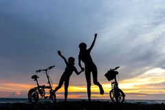 Silhouette freedom biker lovely family at sunset over the ocean. Royalty Free Stock Image