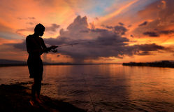 Silhouette  of freedom fishing man. In sunset time lowlight and black dark shadow Royalty Free Stock Photography