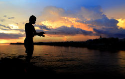 Silhouette  of freedom fishing man. In sunset time lowlight and black dark shadow Stock Images
