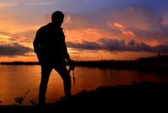 Silhouette  of freedom photographer action. With camera in sunset time dark and lowlight on the mountain view Stock Images