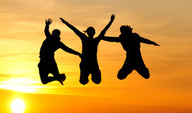 Silhouette of friends jumping Stock Image