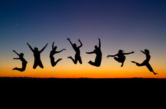 Silhouette of friends jumping Stock Photo