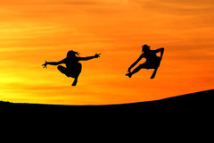 Silhouette of friends jumping in sunset Royalty Free Stock Images