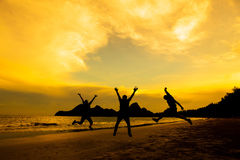 Silhouette of friends jumping Stock Photos