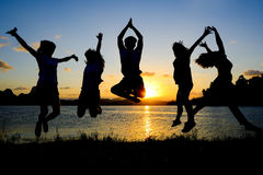 Silhouette of friends jumping in sunset Stock Image