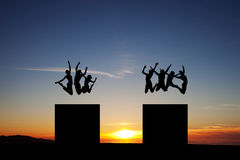 Silhouette of friends jumping on towers Stock Photography