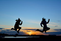 Silhouette in front of sunset. Silhouette of 2 jumping people in front of sunset in Howth bay, Dublin, Ireland Stock Photography