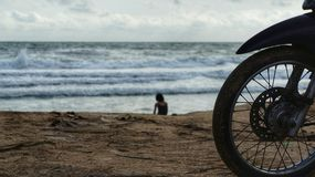 Silhouette of front wheel of motorbike at beach with woman on the beach Stock Images