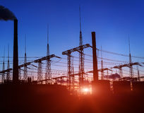 Silhouette of gas turbine electrical power plant against sunset. stock images
