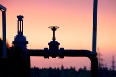 Silhouette of the gas valve on the background of an autumn sunset royalty free stock images