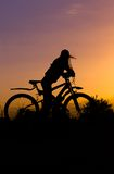 Silhouette of a gerl with a bicycle against the sky at sunset, Stock Photography