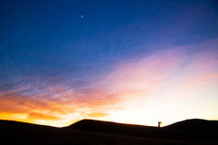 The silhouette of girl. In the dusk.She is waving the fabric Royalty Free Stock Photo