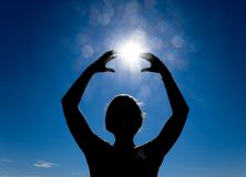 Silhouette of a girl against the background of the sun and blue sky. Hands are raised up to the sun royalty free stock photo