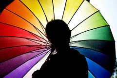 Young woman under an colorful umbrella. Silhouette of a girl against a rainbow umbrella. Young woman walking under bright umbrella stock photo