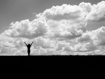 Silhouette of a girl with arms up. High contrast black and white photograph Royalty Free Stock Images