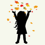 Silhouette girl and autumnal leaves Stock Images