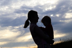 Silhouette of a girl with a baby. Silhouette of a girl with a baby in the evening on the nature Royalty Free Stock Images