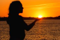 Silhouette of a girl on the background of the evening sun, red sunset. Silhouette of a girl on the background of the evening sun red sunset, keeps the sun in his stock photography