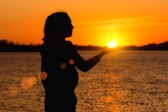 Silhouette of a girl on the background of the evening sun, red sunset. Silhouette of a girl on the background of the evening sun red sunset, keeps the sun in his royalty free stock photography