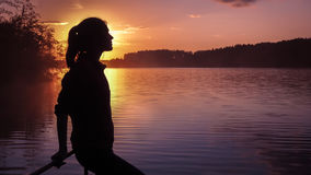 Silhouette girl background sun. Girl standing near water outdoors. Gold sunset lake. Young woman thinking about something river du stock photo
