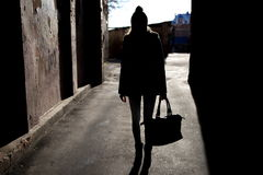 Silhouette of a girl with a bag. On the street. Bright light in the background Stock Images