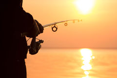 Silhouette of a girl on the bank of the river with a fishing rod Stock Photo