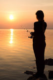 Silhouette of a girl on the bank of the river with a fishing rod Stock Image