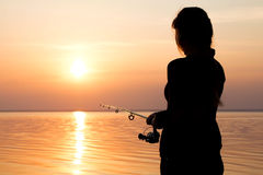 Silhouette of a girl on the bank of the river with a fishing rod Stock Images