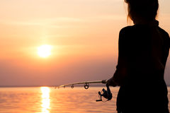 Silhouette of a girl on the bank of the river with a fishing rod Royalty Free Stock Photos