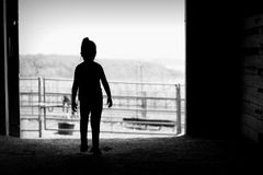 Silhouette of girl in barn door Royalty Free Stock Photos
