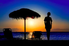 Silhouette of a girl on the beach Stock Images